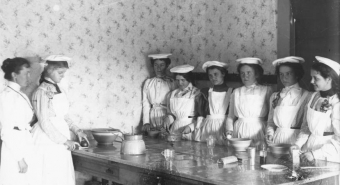 Uniformed Domestic Science students in 1898 teaching kitchen.