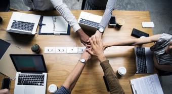 Team of professionals hands together over desk and laptops