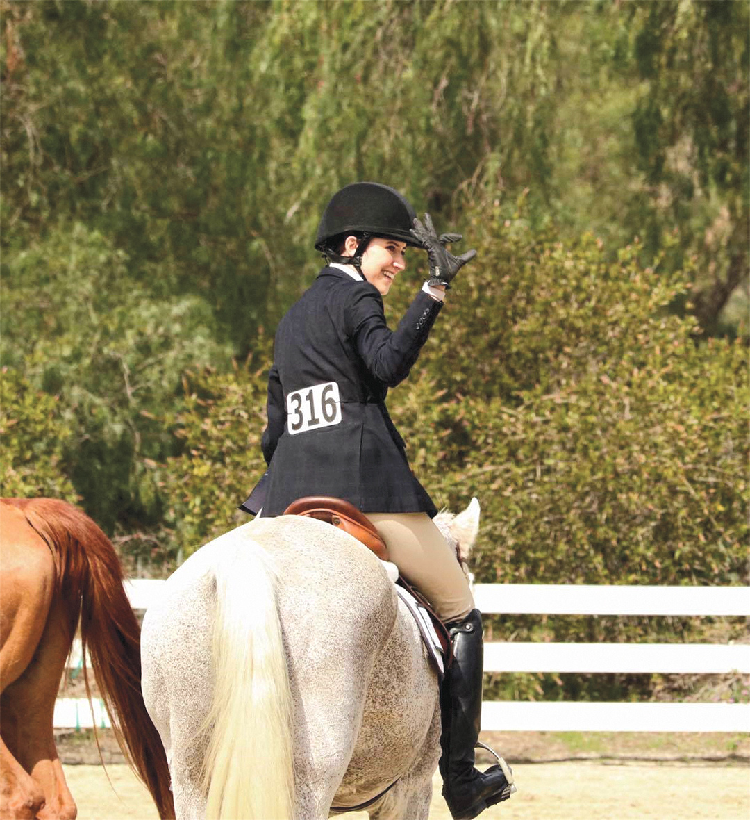 Arizona Parker throwing up the Wildcat sign after placing first at Regionals representing the University of Arizona Equestrian Team.